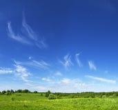Σύννεφα πέρα από το πράσινο λιβάδι Στοκ Εικόνες