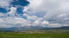Σύννεφα πέρα από το πράσινο λιβάδι με τα μεγαλοπρεπή βουνά στο υπόβαθρο φιλμ μικρού μήκους