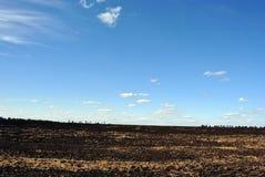 Σύννεφα σε έναν μπλε ουρανό άνοιξη πέρα από ένα οργωμένο φυτόχωμα τομέων Στοκ φωτογραφίες με δικαίωμα ελεύθερης χρήσης