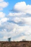 Σύννεφα σωρειτών στον ουρανό πέρα από τα κτήρια και τα ξύλα στοκ εικόνα με δικαίωμα ελεύθερης χρήσης