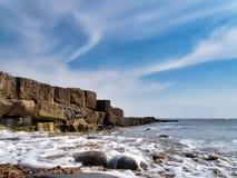 Σύννεφα Swirly και αφρός θάλασσας - Lyme REGIS στοκ εικόνα