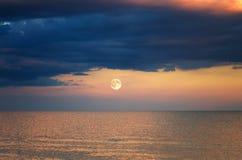 Σύννεφο θύελλας πέρα από τη θάλασσα Ηλιοβασίλεμα Άνοδος φεγγαριών Στοκ Εικόνες