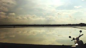 Σύννεφο και ουρανός που απεικονίζονται στο νερό με τη σκιαγραφία του εκλεκτής ποιότητας ποδηλάτου - αλατισμένο αγρόκτημα Ταϊλάνδη στοκ φωτογραφία με δικαίωμα ελεύθερης χρήσης