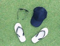 Σύνολα καπέλου, γυαλιών ηλίου και πτώσεων κτυπήματος στην πράσινη χλόη Στοκ Φωτογραφίες