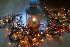 Σύνολο άσπρου φαναριού με τα φω'τα Χριστουγέννων και καλάμων καραμελών στο ξύλινο πάτωμα Στοκ Εικόνες