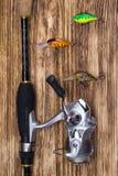 Σύνολο αλιείας σε ένα ξύλινο υπόβαθρο: συλλεχθείσα περιστροφή και δόλωμα υπό μορφή πολύχρωμων μικρών ψαριών στοκ φωτογραφίες