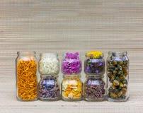 Σύνολο βάζων γυαλιού με τα διαφορετικά λουλούδια, τα πέταλα και τα χορτάρια για τη aromatherapy και εναλλακτική ιατρική Στοκ Φωτογραφίες