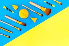 Σύνολο βουρτσών για applicator makeup και σκιάς ματιών στην μπλε και κίτρινη τοπ άποψη υποβάθρου copyspace Στοκ εικόνα με δικαίωμα ελεύθερης χρήσης