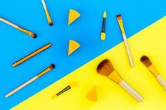 Σύνολο βουρτσών για applicator makeup και σκιάς ματιών στην μπλε και κίτρινη τοπ άποψη υποβάθρου Στοκ Εικόνες