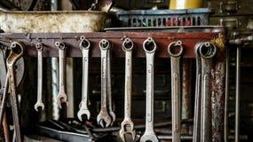 Σύνολο βρώμικων κλειδιών γαλλικών κλειδιών στο ξύλινο ράφι με το διαφορετικό Τ στοκ εικόνα