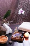 Σύνολο για τις διαδικασίες SPA στον πίνακα, τις πετσέτες υφασμάτων, τα άλατα λουτρών, τις πέτρες μασάζ και το βιο-λάδι Ανθίζοντας Στοκ Φωτογραφία
