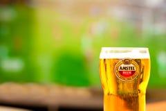Σύνολο γυαλιού Amstel κινηματογραφήσεων σε πρώτο πλάνο της μπύρας - υπόβαθρο του παίζοντας ποδοσφαιρικού παιχνιδιού TV Ασφάλιστρο στοκ εικόνες