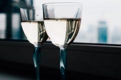 Σύνολο δύο γυαλιών του άσπρου κρασιού σε μια στρωματοειδή φλέβα παραθύρων Στοκ Φωτογραφία
