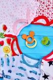 Σύνολο ενδυμάτων και παιχνιδιών μωρών στη μέση Στοκ Εικόνες