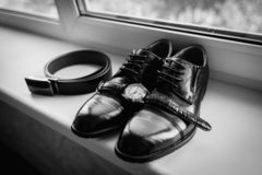 Σύνολο εξαρτημάτων νεόνυμφων στη ημέρα γάμου Γαμήλιες λεπτομέρειες Παπούτσια των ατόμων δέρματος με το δεσμό ζωνών και τόξων εξαρ στοκ φωτογραφίες