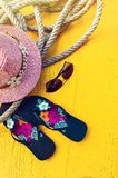 Σύνολο εξαρτημάτων πραγμάτων γυναικών ` s στο κίτρινο υπόβαθρο τοπ άποψης καπέλων γυναικών ` s παραλιών αχύρου εποχής παραλιών στοκ φωτογραφία