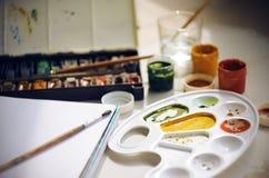 Σύνολο εξαρτημάτων τέχνης για το σχέδιο: χρώματα, βούρτσες, sketchbook, παλέτα και ένα φλυτζάνι του νερού στοκ εικόνα