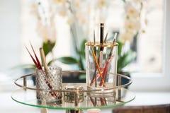 Σύνολο επαγγελματικών βουρτσών σύνθεσης στα εμπορευματοκιβώτια γυαλιού στον πίνακα γυαλιού στο σαλόνι ομορφιάς Στοκ Φωτογραφία