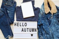 Σύνολο θηλυκών ενδυμάτων φθινοπώρου, σύγχρονος πίνακας με το φθινόπωρο `, κενό σημειωματάριο κειμένων ` γειά σου Τοπ όψη στοκ εικόνα