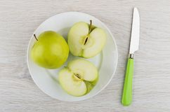Σύνολο και μισά των πράσινων μήλων στο άσπρο πιάτο, μαχαίρι Στοκ Φωτογραφίες