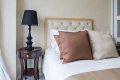 σύνολο καφετιών μαξιλαριών στο κρεβάτι στην κλασική κρεβατοκάμαρα Στοκ Φωτογραφία