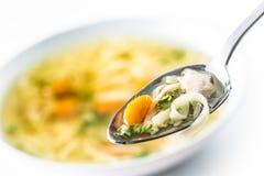 Σύνολο κουταλιών της σούπας κοτόπουλου ή βόειου κρέατος με το καρότο και τα χορτάρια νουντλς στοκ φωτογραφίες