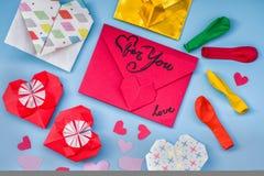 Σύνολο κόμματος ζωηρόχρωμων μπαλονιών, καρδιές εγγράφου origami, υπόβαθρο φακέλων onblue Σύνολο ημέρας βαλεντίνων Στοκ Εικόνες