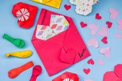 Σύνολο κόμματος ζωηρόχρωμων μπαλονιών, καρδιές εγγράφου origami, υπόβαθρο φακέλων onblue Σύνολο ημέρας βαλεντίνων Στοκ Φωτογραφία