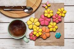 Σύνολο μπισκότων πιπεροριζών στην τσάντα εγγράφου, το κουταλάκι του γλυκού και το φλυτζάνι του καυτού τσαγιού Στοκ Φωτογραφία