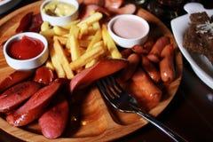 Σύνολο μπύρας Τηγανιτές πατάτες, μίγμα λουκάνικων, ψωμί σκόρδου, δίκρανο, ξύλο Στοκ Εικόνες