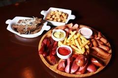 Σύνολο μπύρας Τηγανιτές πατάτες, μίγμα λουκάνικων, ψωμί σκόρδου, stew μπιζέλια, Στοκ εικόνες με δικαίωμα ελεύθερης χρήσης