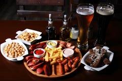 Σύνολο μπύρας Τηγανιτές πατάτες, μίγμα λουκάνικων, ψωμί σκόρδου, stew μπιζέλια Στοκ Φωτογραφία