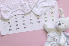 Σύνολο νεογέννητων εξαρτημάτων σε αναμονή για το παιδί - ημερολόγιο με τον αριθμό 14 δεκατέσσερα, ενδύματα μωρών, παιχνίδια στο ρ στοκ εικόνες