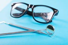 Σύνολο οδοντιατρικής εργαλείων και γυαλιών στο μπλε υπόβαθρο Στοκ εικόνα με δικαίωμα ελεύθερης χρήσης