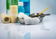Σύνολο σαλτσών προσοχής πληγών και λεκάνη ανοξείδωτου, λαβίδες, μπουκάλι οινοπνεύματος, κανονικός αλατούχος, συνεκτικός ελαστικός στοκ φωτογραφία