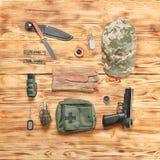 Σύνολο στρατιωτικού εξοπλισμού στο ξύλινο υπόβαθρο στοκ εικόνες