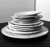 Σύνολο άσπρων κεραμικών πιάτων ανακούφισης γευμάτων στο μαύρο υπόβαθρο Στοκ φωτογραφία με δικαίωμα ελεύθερης χρήσης