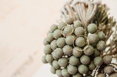 Σύνολο γαμήλιων χρυσών δαχτυλιδιών στα γκρίζα λουλούδια ανθοδεσμών στο βάζο αγροτικό ύφος, μπεζ υπόβαθρο στοκ φωτογραφία