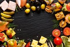 Σύνολο διαφορετικών νόστιμων ορεκτικών, πρόχειρων φαγητών και συστατικών σε ένα μαύρο υπόβαθρο Στοκ εικόνα με δικαίωμα ελεύθερης χρήσης
