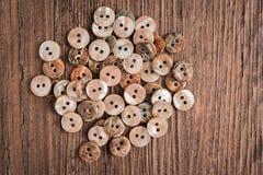 Σύνολο διαφορετικών χρωματισμένων κουμπιών πέρα από την αγροτική ξύλινη σύσταση Στοκ εικόνες με δικαίωμα ελεύθερης χρήσης