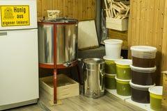 Σύνολο κάδων του αποσπασματικού μελιού από τον εξοπλισμό φυγοκεντρωτών και μελισσοκόμων - κίτρινο γερμανικό σημάδι που λέει το σπ Στοκ εικόνες με δικαίωμα ελεύθερης χρήσης