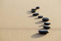 Σύνολο καυτής πέτρας στην άσπρη ήρεμη παραλία άμμου στη μορφή σπονδυλικών στηλών Sel Στοκ εικόνα με δικαίωμα ελεύθερης χρήσης