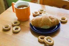 Σύνολο κουπών του μαύρου τσαγιού με το λεμόνι, croissant στο πιάτο και μικρά bagels Στοκ εικόνες με δικαίωμα ελεύθερης χρήσης