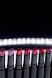 Σύνολο κραγιόν μεταλλινών στα κόκκινα και φυσικά χρώματα στο άσπρο μαύρο υπόβαθρο Ζωηρόχρωμα κραγιόν μόδας Επαγγελματικό makeup b Στοκ Φωτογραφίες