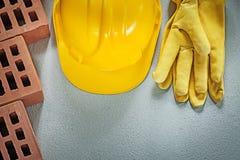 Σύνολο κόκκινων γαντιών ασφάλειας καπέλων τούβλων σκληρών στο συγκεκριμένο υπόβαθρο Στοκ Εικόνες