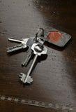 Σύνολο κλειδιών σπιτιών στον καφετή ξύλινο πίνακα Στοκ φωτογραφίες με δικαίωμα ελεύθερης χρήσης