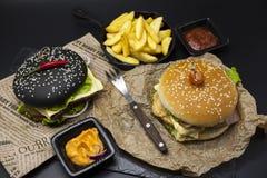 Σύνολο μαύρο burger και κλασσικό αμερικανικό burger Μαύρες burger φέτες ρόλων του juicy μαρμάρινου βόειου κρέατος, λιωμένο τυρί,  Στοκ φωτογραφία με δικαίωμα ελεύθερης χρήσης