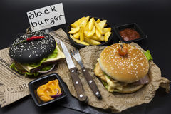 Σύνολο μαύρο burger και κλασσικό αμερικανικό burger Μαύρες burger φέτες ρόλων του juicy μαρμάρινου βόειου κρέατος, λιωμένο τυρί,  Στοκ Εικόνες