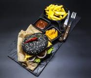 Σύνολο μαύρο burger Πέτρινο πιάτο με: μαύρες burger φέτες ρόλων του juicy μαρμάρινου βόειου κρέατος, λιωμένο τυρί, φρέσκια σαλάτα Στοκ Φωτογραφίες