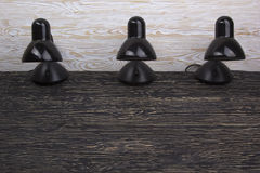 σύνολο μαύρων επιτραπέζιων λαμπτήρων στο ξύλινο υπόβαθρο Στοκ Εικόνα